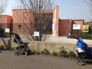 Passeggini di fronte alla scuola di Via Allievi che originariamente era prevista ospitasse un asilo nido